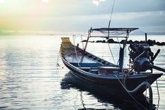 Заход солнца над морем с причаленной традиционной азиатской рыбацкой лодкой в спокойном море Стоковое Изображение RF