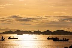 Заход солнца на море с рыбной ловлей шлюпки силуэтов Стоковые Фотографии RF