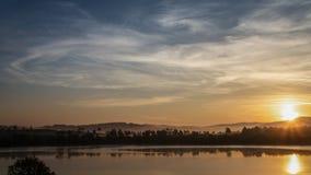 Заход солнца на озере, облачное небо утра Стоковые Изображения