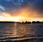 Заход солнца на озере с деревьями на береге Стоковое Изображение