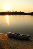Заход солнца на озере с резиновой шлюпкой на береге Стоковая Фотография