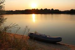 Заход солнца на озере с резиновой шлюпкой на береге Стоковые Фото