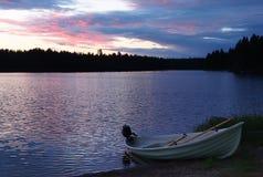 Заход солнца на озере с рыбацкой лодкой на береге в Финляндии Стоковая Фотография