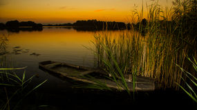 Заход солнца на озере с старой развалиной шлюпки Стоковые Фотографии RF
