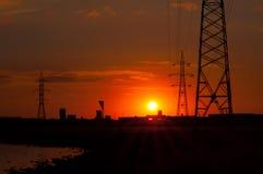 Заход солнца над озером и опорами линии электропередач стоковая фотография