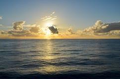 Заход солнца над океаном через облака Стоковая Фотография RF
