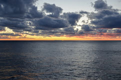 Заход солнца над океаном через облака Стоковые Фото