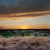 Заход солнца на предпосылке зеленых холмов Стоковые Фото