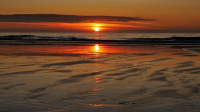 Заход солнца над пляжем, светлое отражение в влажном песке Стоковые Изображения