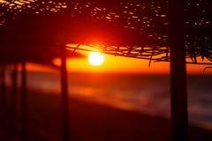 Заход солнца на пляже заходящее солнце среди зонтиков деревянных ручек Стоковое Изображение