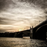 Заход солнца на реке с мостом Стоковое Фото