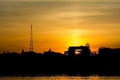 Заход солнца над силуэтом города около воды стоковое фото rf