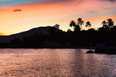Заход солнца на тропическом пляже с ладонями и силуэтом и морем холмов струится на ярком небе захода солнца апельсина и сини Стоковые Фото