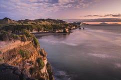 Заход солнца над утесами берега моря и держателем Taranaki, Новой Зеландией Стоковые Изображения