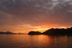 Заход солнца острова на море Стоковая Фотография