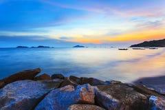 Заход солнца по побережью с море облицовывает предпосылку Стоковая Фотография