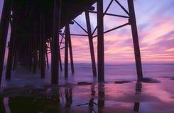 Заход солнца под пристанью Стоковые Изображения