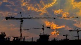 Заход солнца промежутка времени и кран силуэта работая в большой строительной площадке (сигнал вне) сток-видео