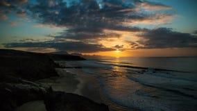 Заход солнца промежутка времени с волнами и облаками на острове Фуэртевентуры, Canaries, Испании видеоматериал