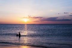 Заход солнца пляжа с людьми ослабляет в сумерк Стоковые Фотографии RF