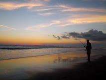 Заход солнца, пляж и человек рыбной ловли Стоковые Фотографии RF