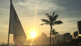 Заход солнца Рио-де-Жанейро Бразилии олимпийского флага порхая акции видеоматериалы