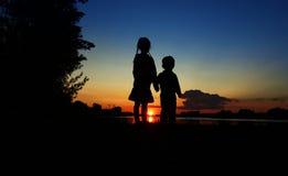 заход солнца силуэта пруда детей Стоковая Фотография