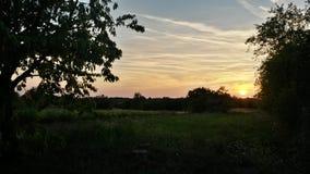 Заход солнца страны над полями Стоковые Изображения