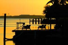 Заход солнца с доком и стульями Стоковые Фото