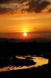 Заход солнца с румяными облаками в небе и реке Стоковая Фотография