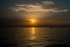 Заход солнца с рыбацкой лодкой на горизонте Стоковое Изображение