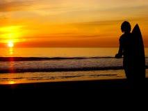 Заход солнца с серфером стоковое изображение rf