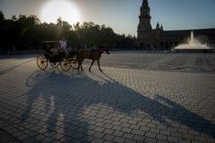 Заход солнца с экипажом лошади на площади de espana в Севилье, Spai Стоковое фото RF
