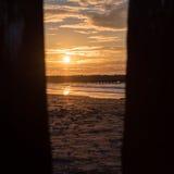 Заход солнца через кучи на пляже Северного моря Cadzand, Голландии Стоковые Изображения