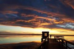 Заход солнца Человек на пристани beautiful clouds Справочная информация стоковая фотография rf
