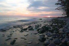 Заход солнца Lake Ontario на пляже с солнцем в расстоянии Стоковые Фото