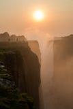 Заход солнца Victoria Falls с туристом в скале Стоковые Фото