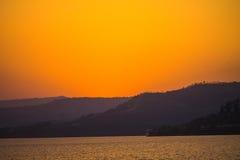 Заходы солнца греют на солнце светлооранжевая гора цвета Стоковые Фото