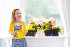 Зацветать маленькой девочки моча цветет дома Стоковая Фотография