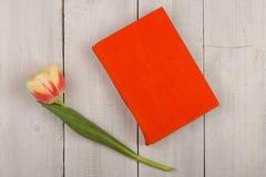 Зацветите книга тюльпана и апельсина на белом деревянном столе Стоковое Изображение RF