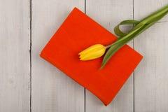 Зацветите книга тюльпана и апельсина на белом деревянном столе Стоковое Фото