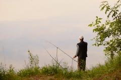 Зацеплять рыболова озеро на зоре Стоковые Фотографии RF