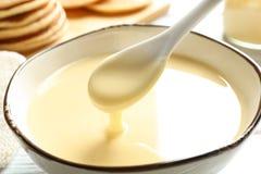 Зачерпните ложкой лить сконденсированное молоко над шаром на таблице, крупном плане стоковая фотография rf