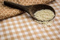 Зачерпните рис ложкой на таблице покрытой с хлопком Стоковые Изображения