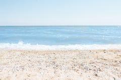 Зашкурьте конец-вверх, на фоне запачканных голубых моря или океана, пустой пляж, солнечный день, пляж с раковинами Стоковые Изображения
