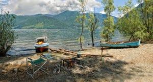 Зашкурьте пляж озера горы с пикником и шлюпками Стоковые Изображения