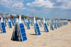 Зашкурьте пляж с голубыми loungers солнца в летнем дне Стоковая Фотография