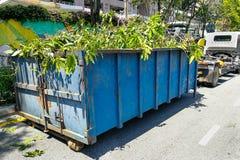 Защелка контейнера отброса с тележкой полной древесин выжимк сада Стоковые Фотографии RF
