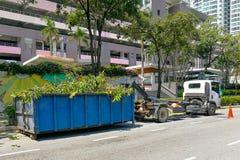 Защелка контейнера отброса с тележкой полной древесин выжимк сада Стоковые Фото
