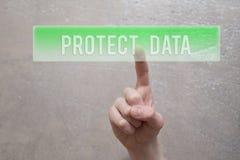 Защитите данные - палец отжимая зеленую кнопку стоковые изображения